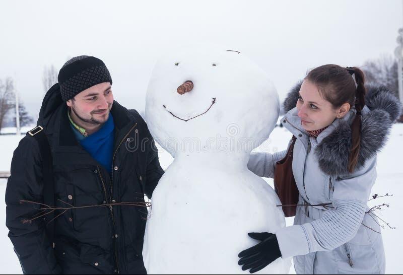 De wintervermaak - het paar beeldhouwt sneeuwman stock foto