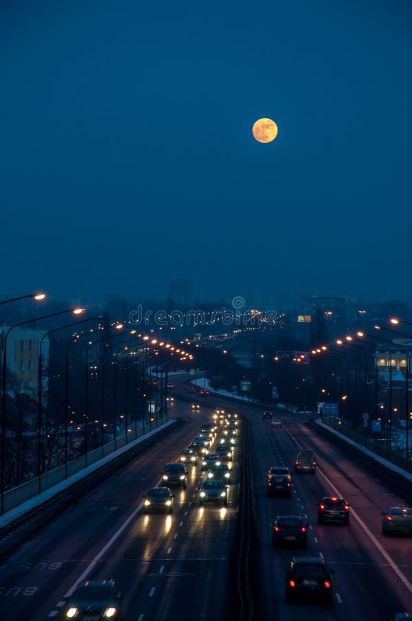 De wintervolle maan onder de stad stock afbeeldingen