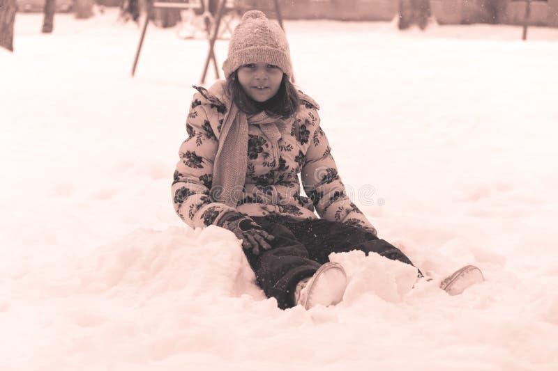 De wintervreugde en pret Het meisje zit op sneeuw stock afbeeldingen
