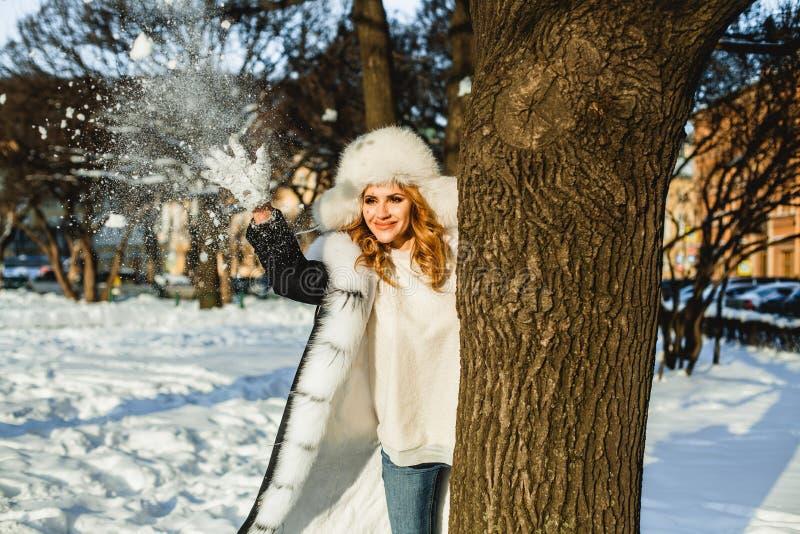 De wintervrouw het spelen sneeuwballen openlucht royalty-vrije stock foto's