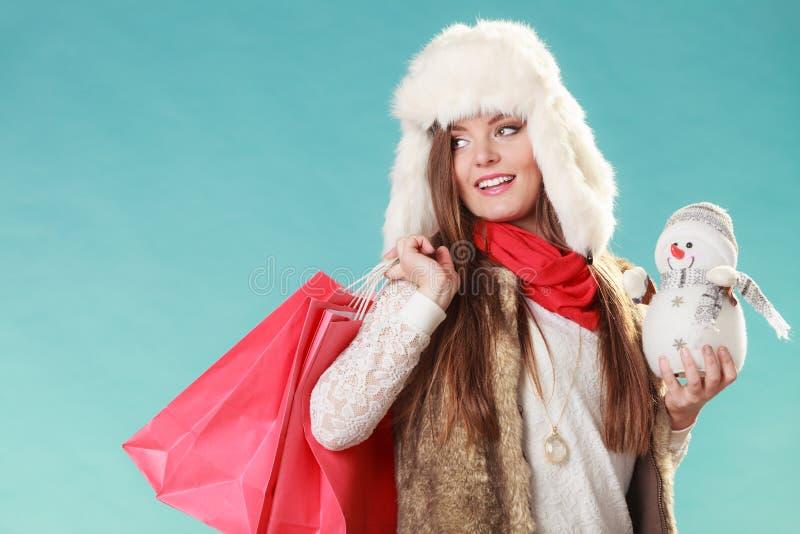 De wintervrouw met weinig sneeuwman en zakken het winkelen royalty-vrije stock afbeelding