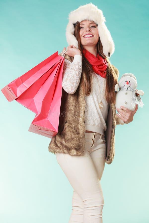 De wintervrouw met weinig sneeuwman en zakken het winkelen royalty-vrije stock fotografie