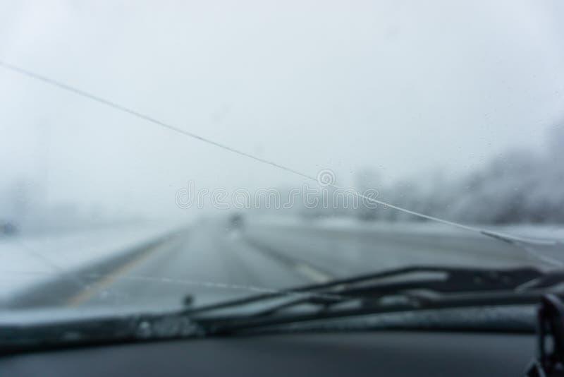 De winterweg gebroken windscherm die op vage wegscène kijken stock foto's