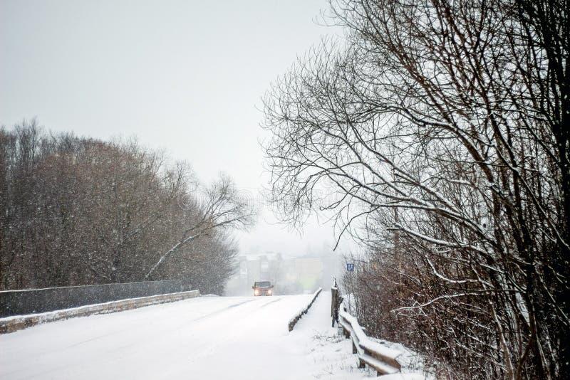 De winterweg in het hout Een auto op de weg met snow_ wordt behandeld die royalty-vrije stock fotografie