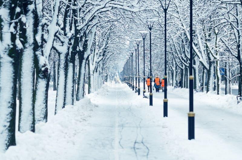 De wissers in oranje vesten lopen langs een sneeuwsteeg stock foto's