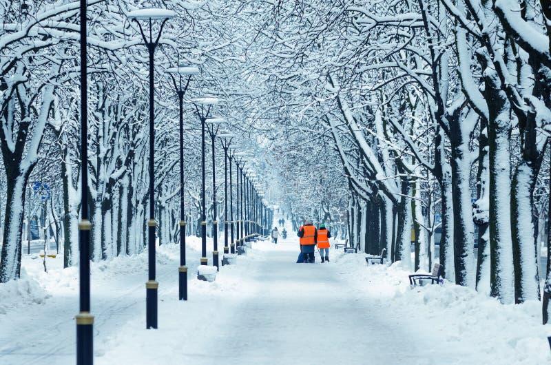 De wissers in oranje vesten lopen langs een sneeuwsteeg royalty-vrije stock afbeeldingen