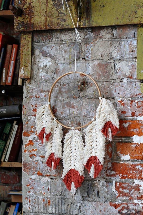 De wit-rode macraméveren hangen op rond dreamcatcher tegen een bakstenen muur naast een boekenkast in de Zolder in Moskou royalty-vrije stock foto's