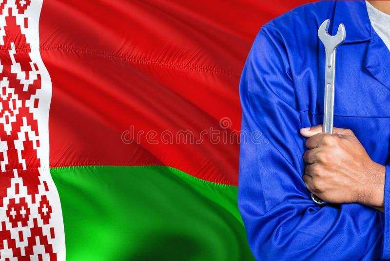 De Witrussische Werktuigkundige in blauwe eenvormig houdt moersleutel tegen golvende Witrussische vlagachtergrond Gekruiste wapen stock afbeeldingen