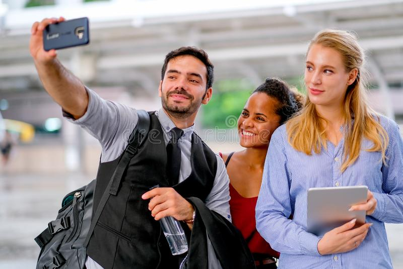 De witte bedrijfsman gebruiks mobiele telefoon aan selfie met gemengde race en witte vrouwen en allemaal kijken gelukkig royalty-vrije stock afbeelding