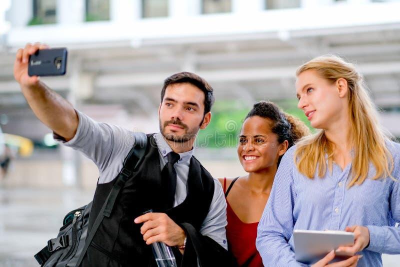 De witte bedrijfsman gebruiks mobiele telefoon aan selfie met gemengde race en witte vrouwen en allemaal kijken gelukkig stock foto