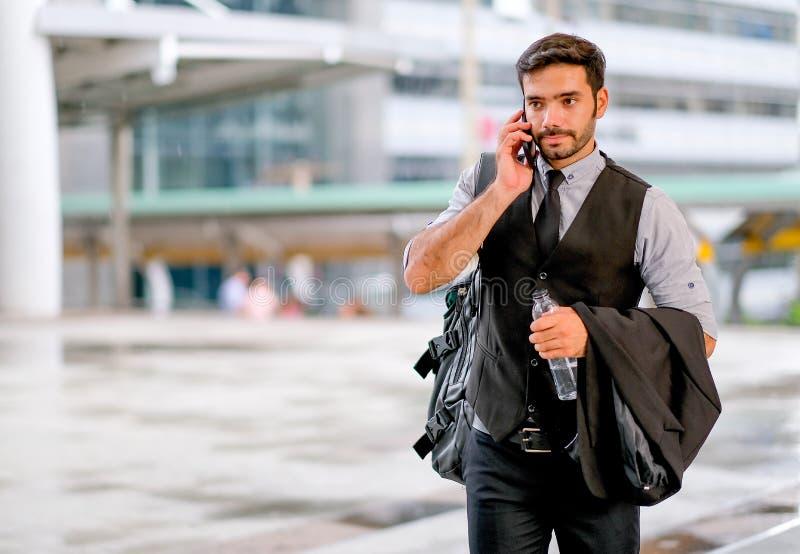 De witte bedrijfsmens houdt de fles water en overhandigt zijn kostuum of jasje op zijn wapen, ook gebruiks mobiele telefoon om te royalty-vrije stock foto's