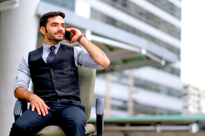 De witte bedrijfsmens zit op de stoel en gebruiks de mobiele telefoon voor het roepen onder de stad tijdens dagtijd stock afbeeldingen