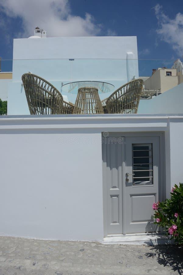 de witte bouw buiten met een grijze die deur en een terras met stoelen en lijst van rijs wordt gemaakt royalty-vrije stock afbeelding