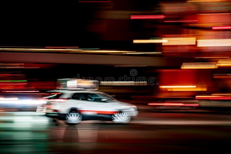De witte cabine van de autotaxi in stad bij nacht met het concept van het motieonduidelijke beeld stock fotografie