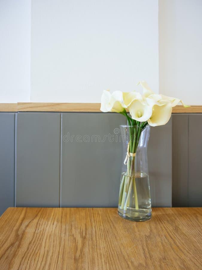 De witte Calla bloemen van Lilly in glasvaas op Lijst stock fotografie