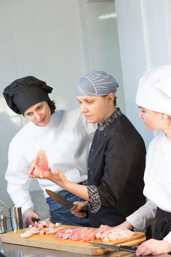 De witte chef-kok onderwijst stagiair om een kip te snijden Hoofdklasse op de achtergrond van de keuken stock foto