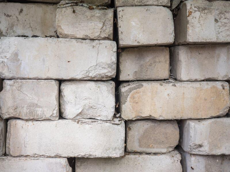De witte die bakstenen van het calciumsilicaat bovenop elkaar worden opgestapeld Oude, gebarsten en afgebroken gebouwde baksteen, stock fotografie