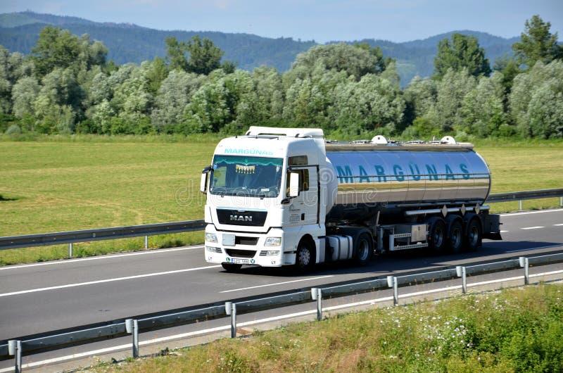 De witte die MENSENvrachtwagen aan tankoplegger wordt gekoppeld drived op Slowaakse D1 weg in platteland stock afbeeldingen
