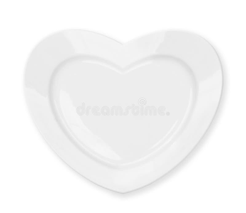 De witte die plaat van de hartvorm met het knippen van weg wordt geïsoleerd stock foto
