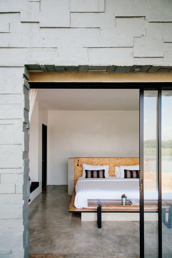 De witte eigentijdse slaapkamer van de hotelstijl met grijze kleurensteen wal royalty-vrije stock foto's