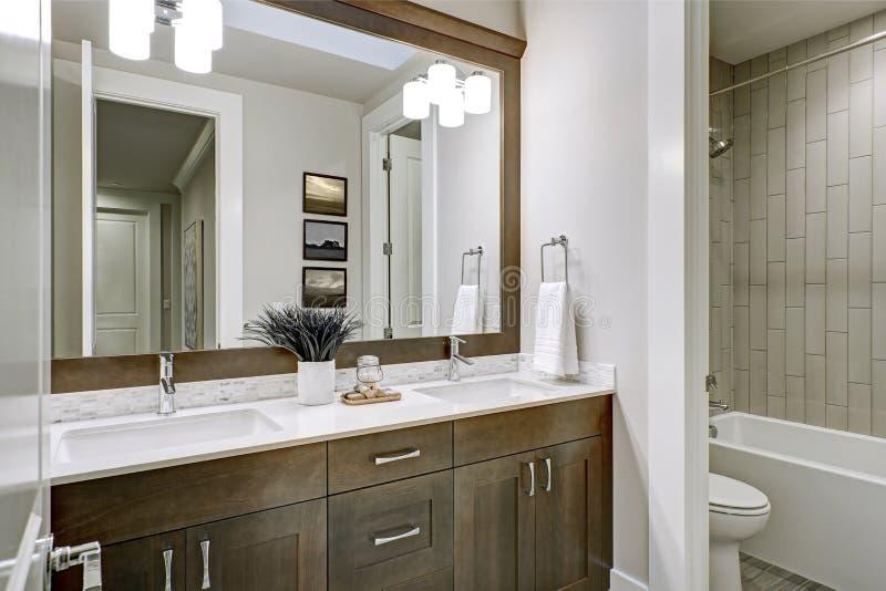 De witte en bruine die badkamers schept een hoekje op met dubbele ijdelheid wordt gevuld royalty-vrije stock foto