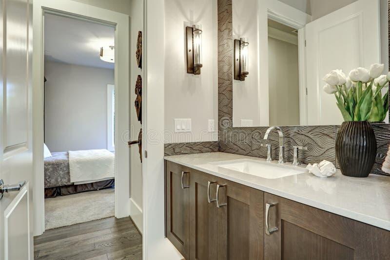 De witte en bruine die badkamers schept een hoekje op met taupeijdelheid wordt gevuld royalty-vrije stock fotografie