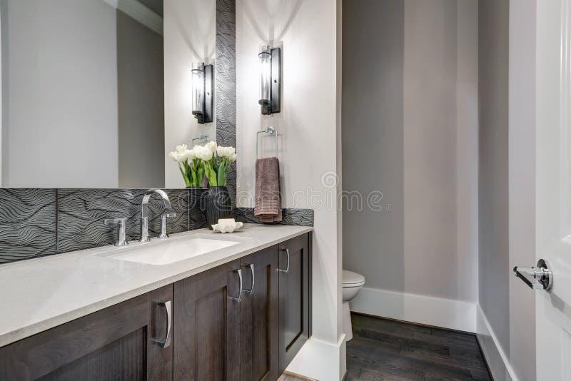 De witte en bruine die badkamers schept een hoekje op met taupeijdelheid wordt gevuld stock foto's