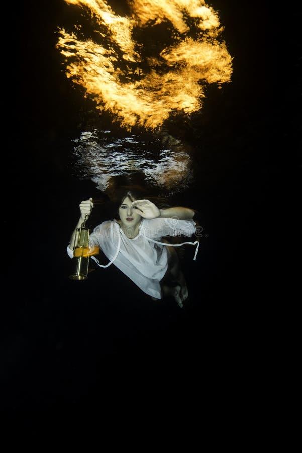 De witte geklede vrouw duikt onderwater met latern royalty-vrije stock fotografie