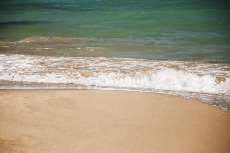 De witte golf van het azuurblauwe overzees wordt gewassen door het zandige strand, exemplaarspase stock afbeeldingen