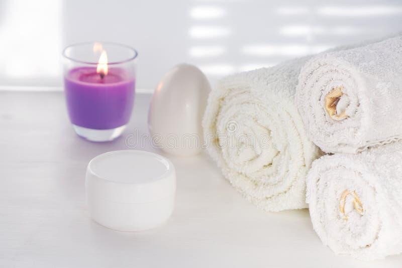 De witte handdoeken bemerkten kaars met de roomkruik van de lavendelgeur op witte achtergrond voor kosmetische procedures royalty-vrije stock foto