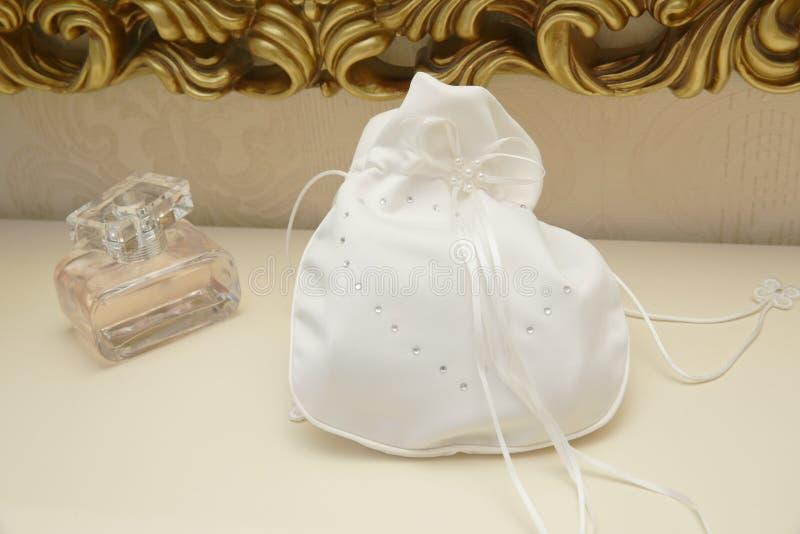 De witte handtas van de huwelijkszijde met bergkristallen en wit lint voor schoonheidsmiddelen en een fles parfum op de toilettaf royalty-vrije stock afbeelding