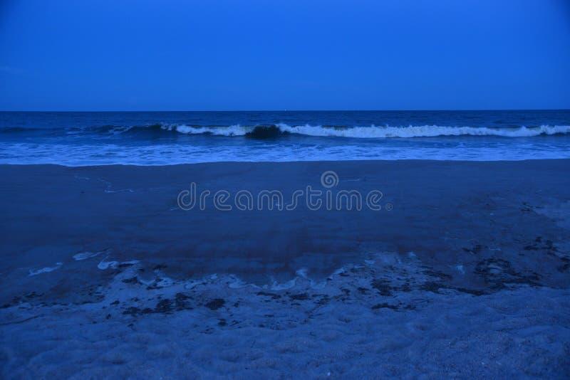 De witte kappen op de inkomende golven glanzen aangezien de duisternis valt royalty-vrije stock fotografie
