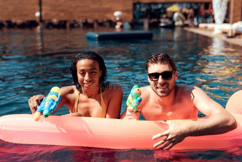 De witte kerel en het zwarte meisje zwemmen met waterkanonnen op opblaasbare matras in pool stock fotografie
