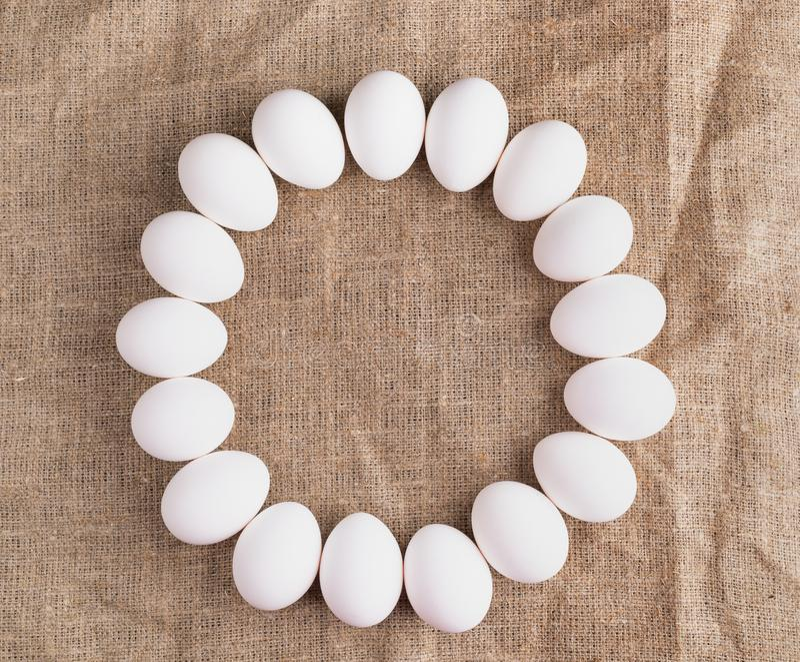De witte kippeneieren liggen in cirkel op ruw canvas stock afbeelding