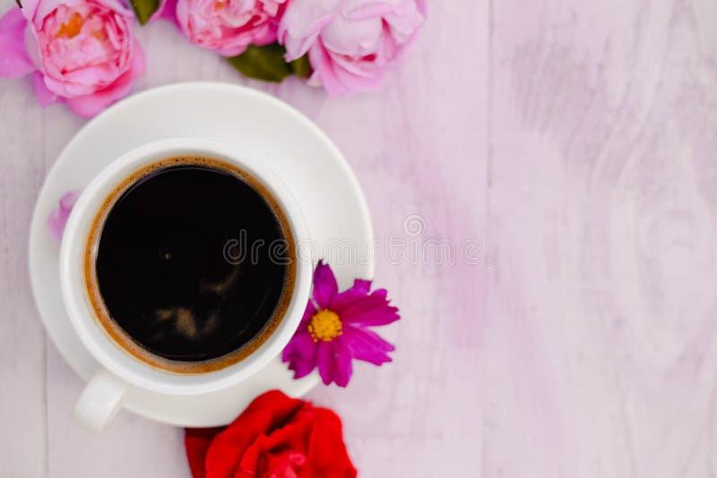 De witte kop van zwarte koffie en nam bloemblaadjes naast toe royalty-vrije stock fotografie
