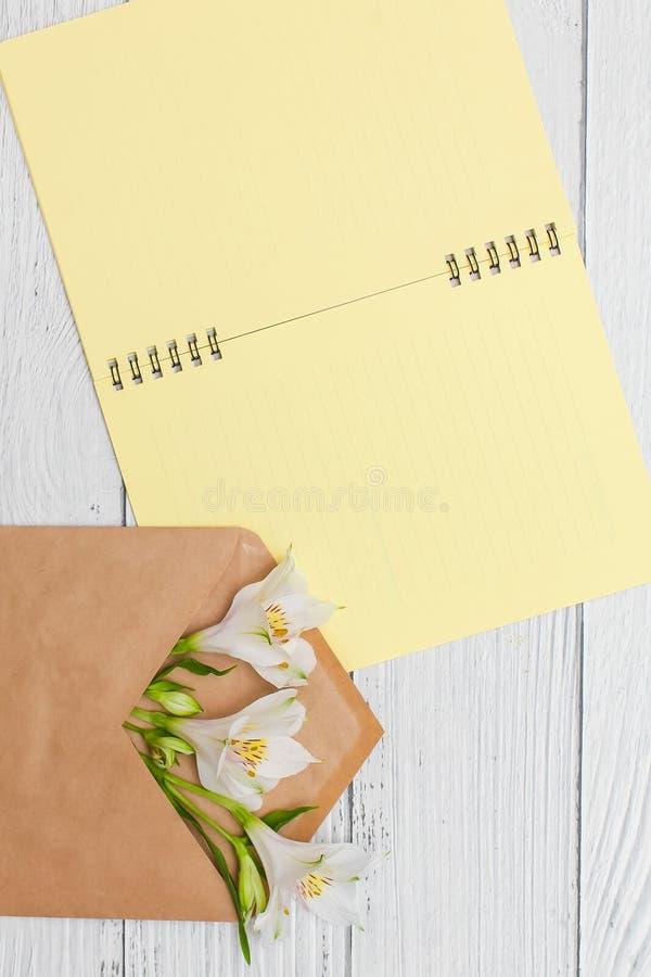 De witte lelies in ambachtenvelop met geel notitieboekje op witte houten lijst, hoogste vlakke mening, leggen stock afbeeldingen