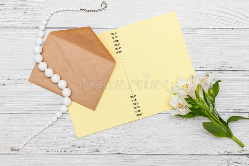 De witte lelies met geel notitieboekje en de parels met ambachtenvelop op witte houten lijst, hoogste vlakke mening, leggen stock afbeeldingen