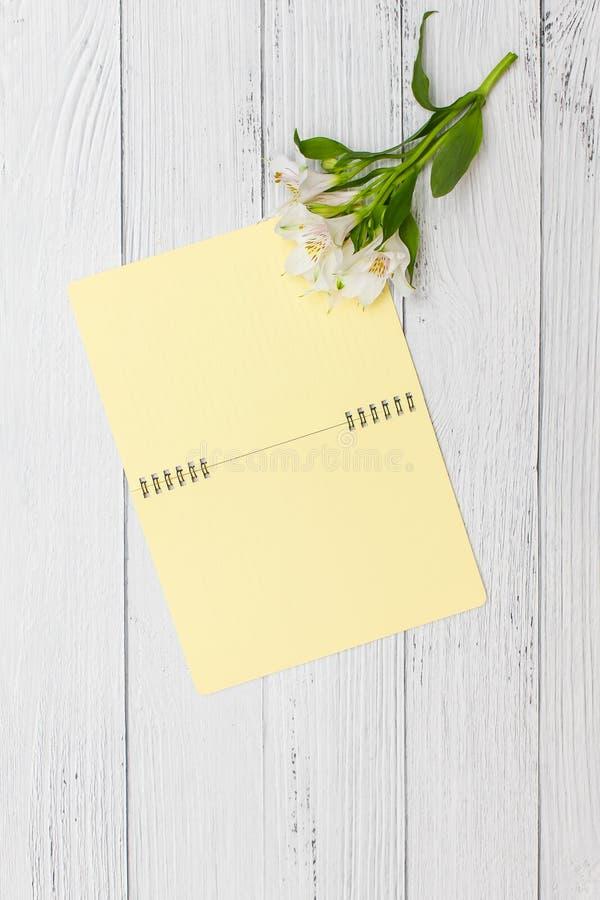 De witte lelies met geel notitieboekje op witte houten lijst, hoogste vlakke mening, leggen royalty-vrije stock afbeelding