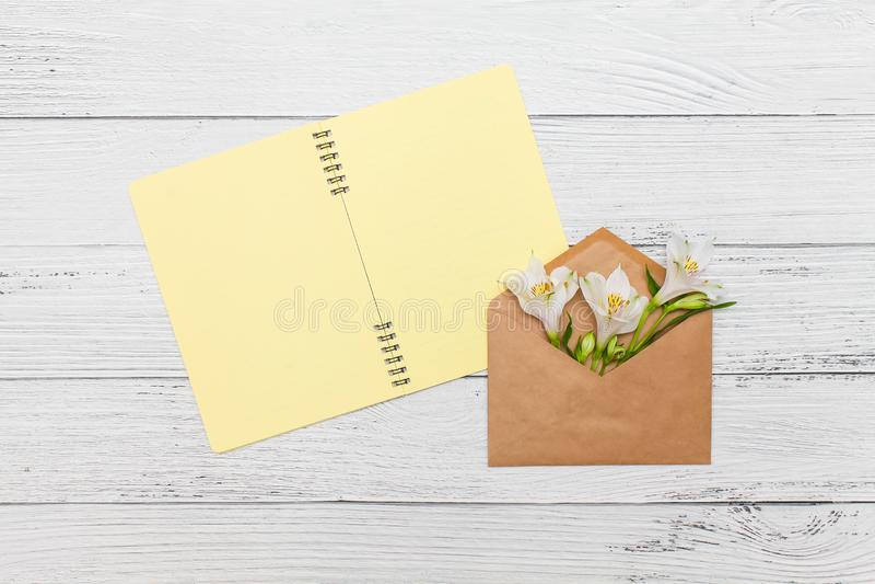 De witte lelies met gele notitieboekje en ambachtenvelop op witte houten lijst, hoogste vlakke mening, leggen stock foto