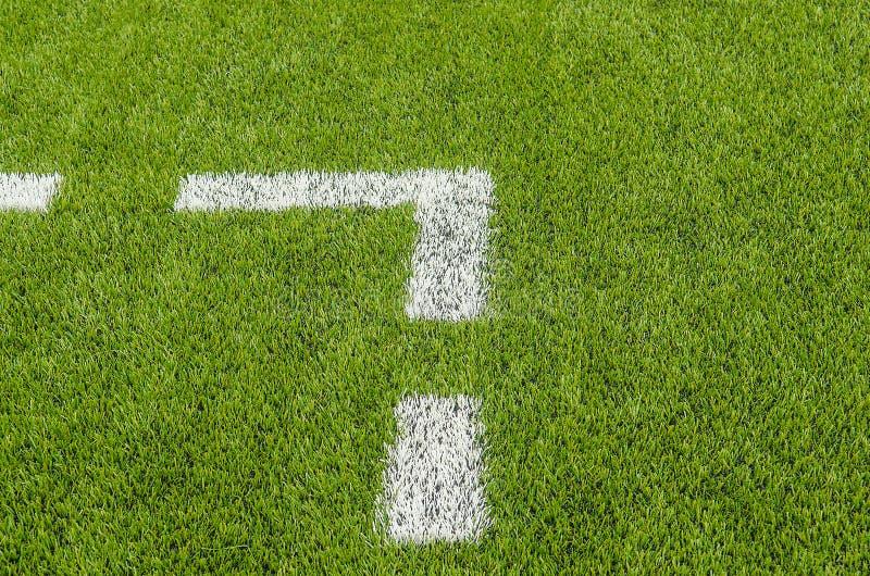 De witte Lijn die op het kunstmatige groene gebied van het grasvoetbal merken stock foto