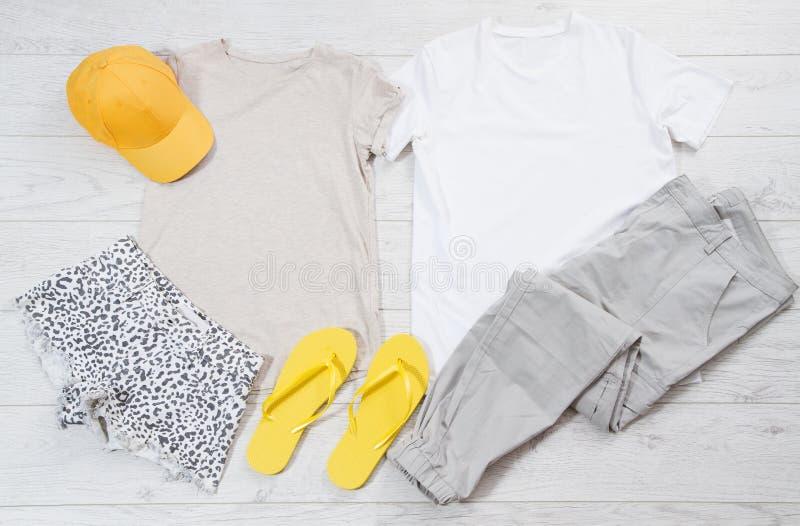 De witte mannelijke en vrouwelijke spot van t-shirtwipschakelaars legt omhoog vlak op houten achtergrond Hoogste mening en exempl stock afbeelding