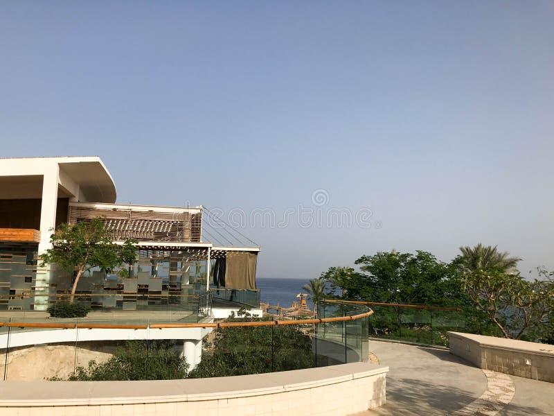 De witte moderne bouw op een berghelling in een overzeese tropische toevlucht tegen een blauwe hemel royalty-vrije stock fotografie