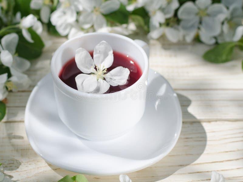 De witte mok thee op een houten lijst, appel komt op de achtergrond tot bloei Zonnig, zijaanzicht royalty-vrije stock fotografie