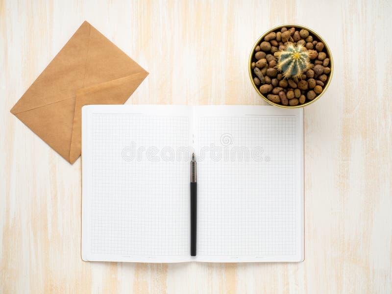 De witte open blocnote, kraftpapier-de envelop en de cactus in pot die op beige houten bureau liggen, leggen vlak, copyspace stock afbeeldingen
