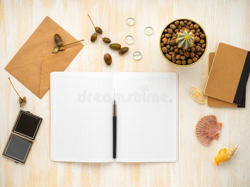 De witte open blocnote, kraftpapier-de envelop en de cactus in pot die op beige houten bureau liggen, leggen vlak, copyspace royalty-vrije stock afbeeldingen