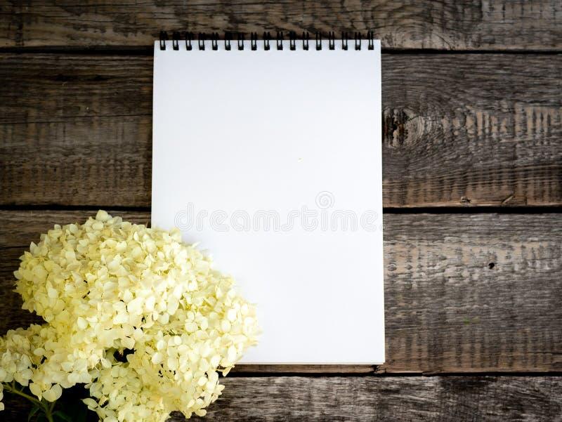 De witte open lege Blocnote en een boeket van bloemen gevoelige purpere hydrangea hortensia op uitstekende oude houten grijze ach royalty-vrije stock fotografie
