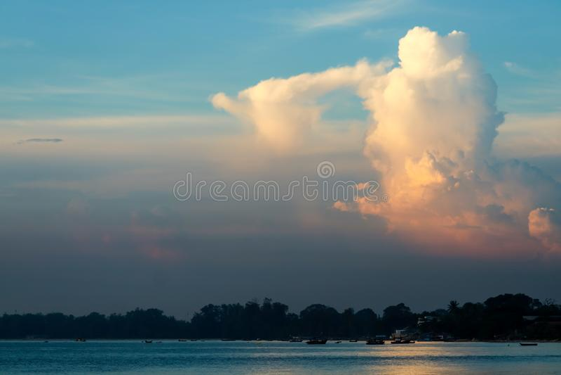de witte oranje zonneschijn van de zonsondergangwolk in blauwe hemel over overzees royalty-vrije stock afbeelding