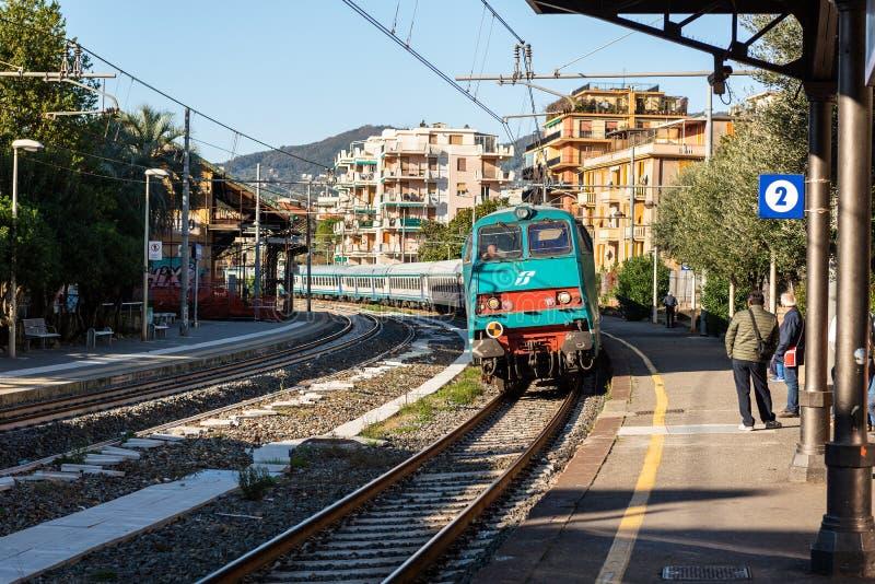 De witte passagierstrein komt aan station aan bij Rapallo-stad, Itali? royalty-vrije stock fotografie