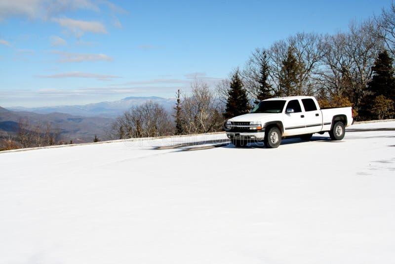 De witte pick-upzitting bovenop een sneeuw behandelde berg met mooie hemel en mening van andere bergen in de afstand stock foto