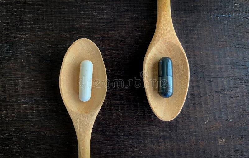 De witte pillen en de zwarte pillen worden geplaatst op een houten lepel die op het oude hout wordt geplaatst royalty-vrije stock fotografie